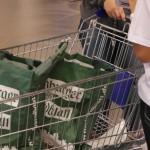 Promoterin packt Taschen in einen Einkaufswagen