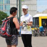 Eine Promoterin von ST-PROMOTIONS verteilt bei einer Samplingaktion in Berlin Produktproben und Flyer an Passanten mit Hund